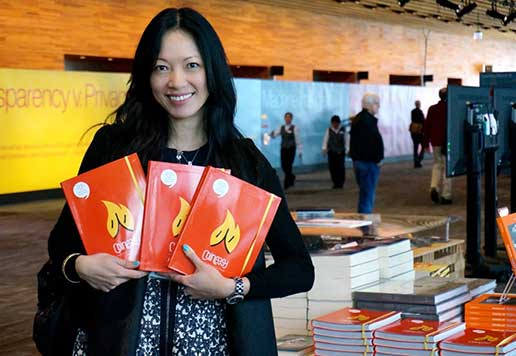 A woman proudly displays the books she launched on Kickstarter